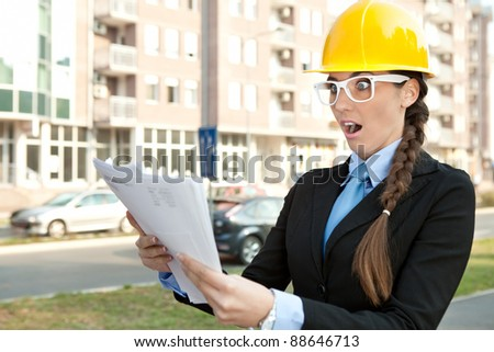 female engineer reading  paperwork , shocked and surprised with information - stock photo