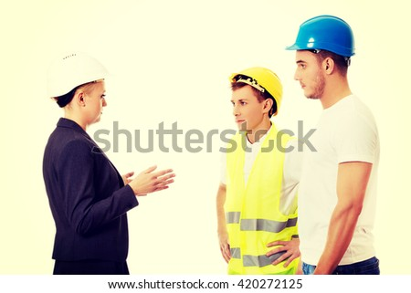 Female engineer talking with two builders - stock photo