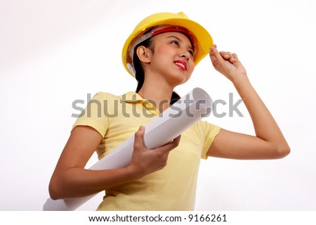 female engineer wearing a hard hat and holding a plan - stock photo