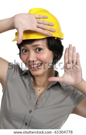 Female Engineer wearing yellow helmet framing her face isolated over white background