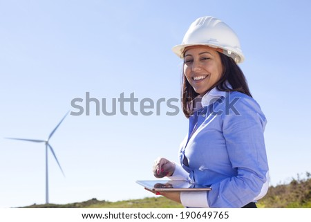 Female engineer working with a tablet at wind farm - stock photo