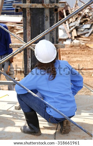 Female engineers are checking the vertical column wood form work in site construction