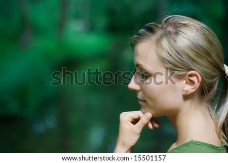 female engrossed in thought - background creek in forrest - stock photo