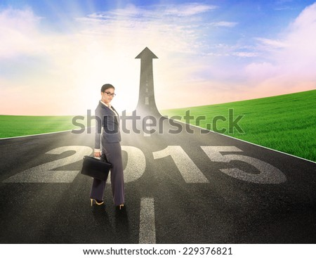Female entrepreneur looking at camera on the road with number 2015 - stock photo