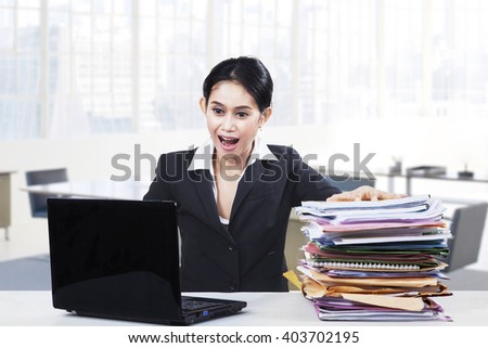 Female entrepreneur looks surprised with a laptop computer and a pile of paperwork on the table in office - stock photo