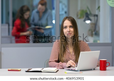 Female Entrepreneur sitting at Office Table with portable Computer and looking into Camera - stock photo