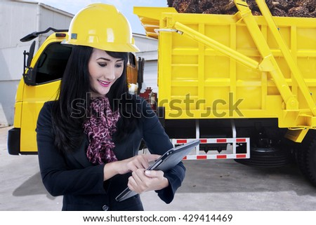 Female entrepreneur using digital tablet with a truck carrying palm fruit on the background - stock photo