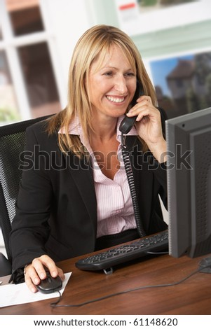 Female Estate Agent Talking On Phone At Desk - stock photo