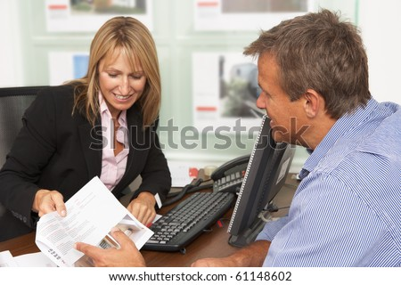 Female Estate Discussing Property Details With Client - stock photo