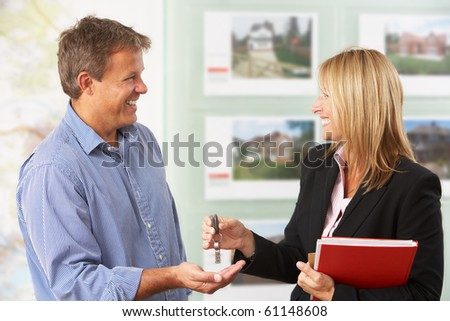 Female Estate Handing Over Keys Of New Home To Client - stock photo