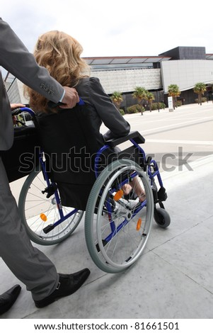 Female executive being pushed in wheelchair - stock photo