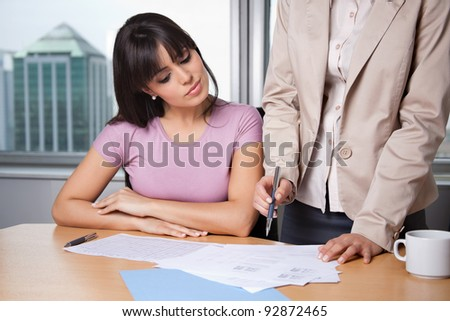 Female executive explaining project plan to her colleague in office - stock photo