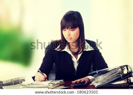 Female executive filling out tax forms while sitting at her desk.  - stock photo