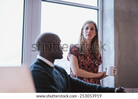 Female executive holding a cup of coffee with male colleague sitting at his desk. Young business people at office. - stock photo