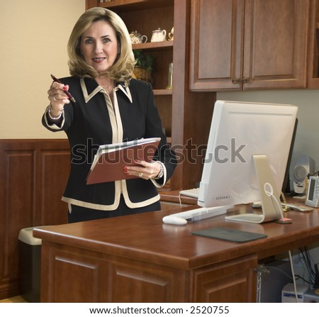 Female executive in her office standing with files - stock photo