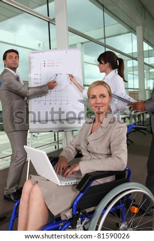 Female executive in wheelchair using laptop computer during presentation - stock photo