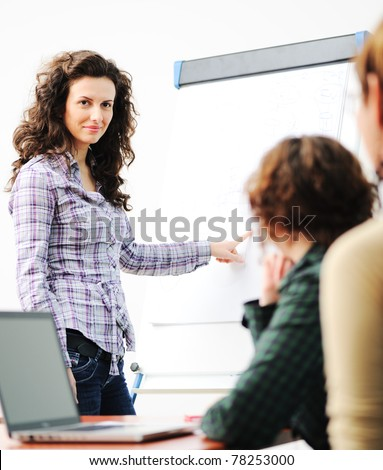 Female executive making  presentation to her colleagues in modern environment - stock photo