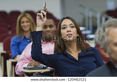 Female executive raising hand during a business lecture amid colleagues - stock photo