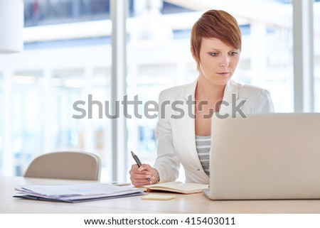 Female executive reading on her laptop while working