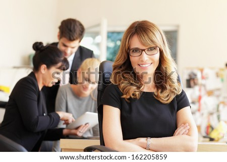 Female executive smiling in the office, with her colleagues in background. Shallow focus.