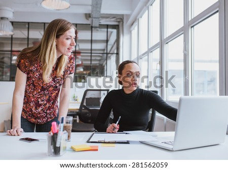 Female executives working together on new project. Creative team using laptop for information in office. - stock photo