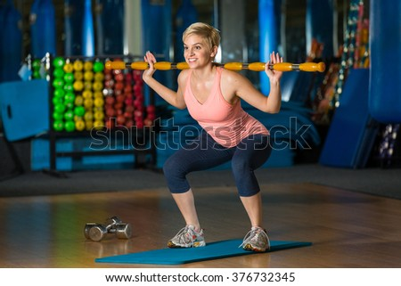 Female exercising her legs with weighted aerobic bar stick workout in nice gym class - stock photo