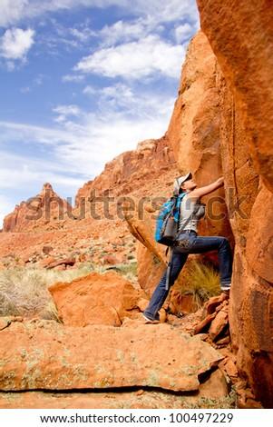 Female explorer at the desert climbing a rocky mountain - stock photo