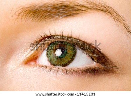 female eye with green contact lenses macro