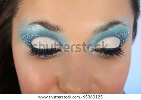 female eyes with blue make-up and crystals