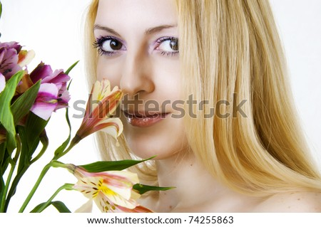 Female face with healthy skin and brown eyes closeup and spring flowers. Skincare, spa and floral concept. - stock photo