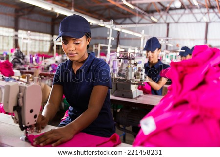 female factory worker sewing with colleagues on background - stock photo