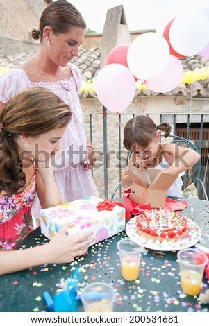 Female family group celebrating a young girl birthday during a summer day, around a table with a birthday cake and gifts and a surprised birthday girl opening a present. Family enjoying outdoors. - stock photo