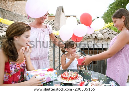 Female family group enjoying and celebrating a young girl child birthday during a summer day, around a table with a birthday cake and gifts and a surprised birthday girl. Family celebrating outdoors. - stock photo