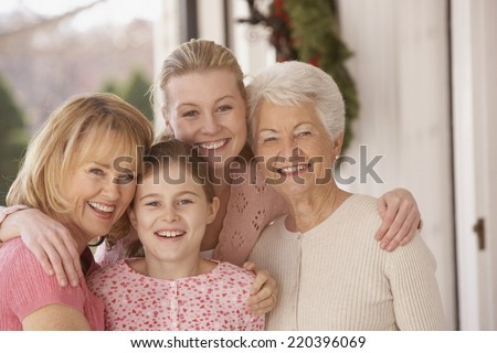 Female family members hugging and smiling - stock photo