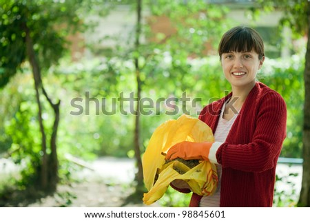 Female farmer fertilizes the soil in garden - stock photo