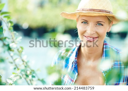 Female farmer in hat looking at camera with smile - stock photo