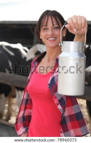female farmer milking the cows - stock photo