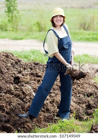 Female farmer spreads manure at farm - stock photo