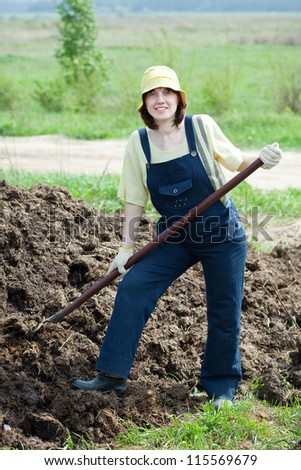Female farmer works with animal manure at field