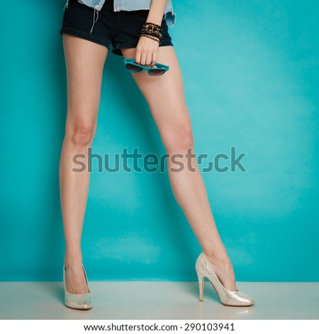 Female fashion. Closeup of silver high heels spiked fashionable shoes on sexy legs on blue. Studio shot. - stock photo