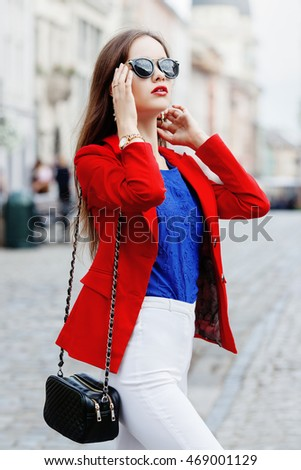 Female fashion concept. Outdoor portrait of a young beautiful confident fashionable woman walking on the street. Model wearing stylish clothes. Girl looking up. Sunny day. City lifestyle. Waist up