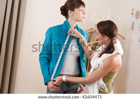 Female fashion designer measuring turquoise jacket on model, taking measurements - stock photo