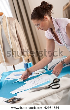 Female fashion designer working at studio with pattern cuttings and sketches - stock photo