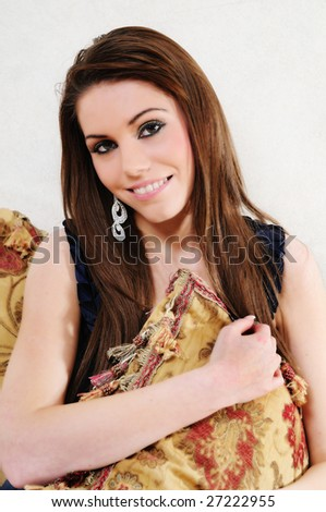 female fashion model clutching on to a large cushion smiling happily at the camera.