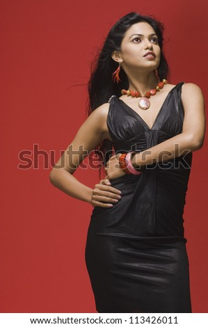 Female fashion model posing against red background