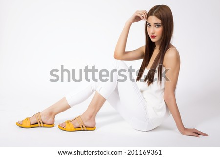 female fashion model wearing white clothes and sitting on the floor   - stock photo