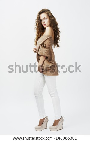 female fashion model wearing white jeans and brown sweater long blond hair  - stock photo