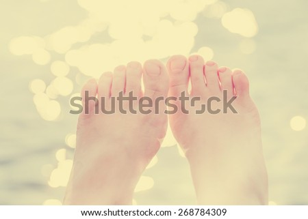 female feet against bokeh water/ selective focus  - stock photo