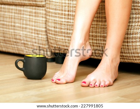 Female feet and a cup of tea or coffee - stock photo