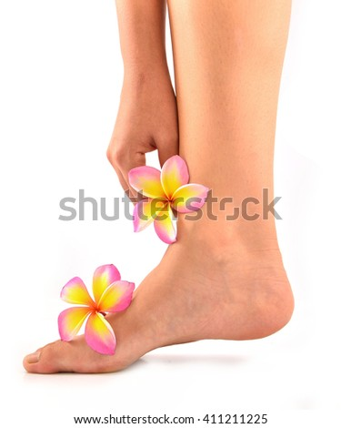 Female feet and hand at spa pedicure procedure with plumeria isolated on white - stock photo